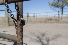 Old Cattle Pen. Iron Chain & Lock on Open Gate. With Prairie in the Background Royalty Free Stock Photos