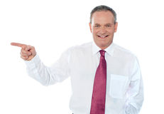 Old caucasian male executive pointing away Stock Photo