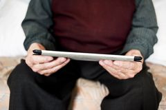 Old caucasian man using a tablet or e-reader stock photo