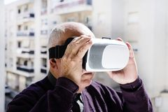 Old caucasian man using a virtual reality headset royalty free stock photos