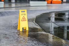 Old caution wet floor warning sign near wet area. With blurred background Royalty Free Stock Image