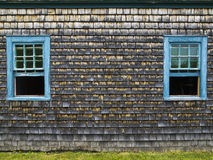 Old cedar weathered shingles wall with two open blue windows Stock Photos