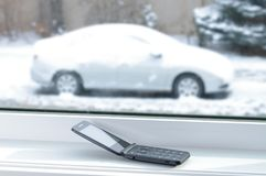 Old cell phone with car in snow Stock Photography