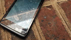 Old cell phone (smartphone) with broken screen on a ground. Old cell phone (smartphone) with broken screen on a brick surface royalty free stock image