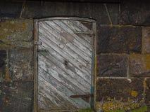 Old cellar door. Worn wooden door on stoned wall Stock Photos