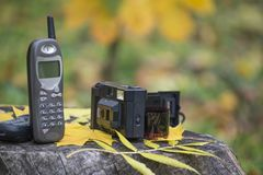Old cellular phone and film camera. Mobile telephone from 90`s and camera from 80`s Royalty Free Stock Photo