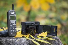 Old cellular phone and film camera. Mobile telephone from 90`s and camera from 80`s. stock photography