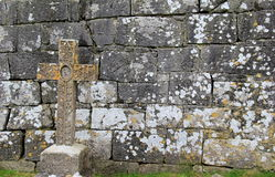 Old Celtic cross leaning against moss and lichen covered stone wall Royalty Free Stock Photos