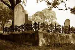 Old cemetery. Old christian cemetery with stone tombstones and intricate iron gate; sepia tones stock photo