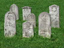 Old cemetery tombstones. Small group of old, worn, and damaged Christian tombstones in grass of a cemetery stock image