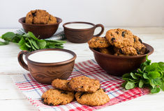 Old ceramic cups of milk and Freshly baked oatmeal raisin cookies in clay bowl Stock Images