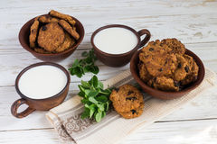 Old ceramic cups of milk and Freshly baked oatmeal raisin cookies in clay bowl Royalty Free Stock Photography