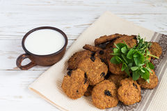 Old ceramic cups of milk and Freshly baked oatmeal raisin cookies in clay bowl Stock Photo