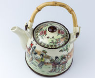 Old ceramic East Asian teapot with drawings. East Asian teapot with bamboo handle and drawings Royalty Free Stock Image