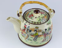 Old ceramic East Asian teapot with drawings. East Asian teapot with bamboo handle and drawings Royalty Free Stock Photography