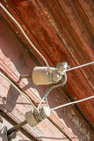 Old Ceramic insulators on the wooden wall. Connection wiring. Royalty Free Stock Image