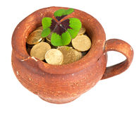 Old ceramic pot with money coins and clover leaf. On white background royalty free stock photo