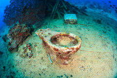 An old ceramic toilet on the sea bed. An old ceramic toilet sits on the sea bed near a coral reef royalty free stock photo