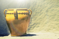 Old ceramics terracotta vase light brown yellow. Background stone wall Royalty Free Stock Photos
