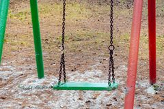Old chain swing outdoor in Park in pine forest. Wooden seat swing seat close up