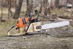 The old chainsaw. The chainsaw is on a wooden beam royalty free stock images