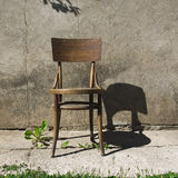 Old Chair. An old chair in a sunny day at the old, cracked wall with a large shadow Stock Image