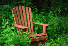 Old Chair. An old adirondack chair in an overgrown wildflower garden stock image
