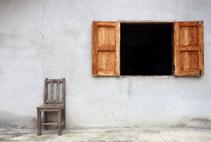 Old chair against old wall with window Stock Image