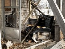 Front porch of an abandoned home with a torn up recliner Stock Image