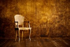 Old chair on a brown wall background. Old chair on a brown wall background royalty free stock photography