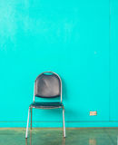 Old chair on concrete green wall Royalty Free Stock Images
