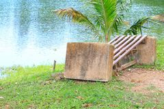Old chair deduct riverside in public park.  royalty free stock photo