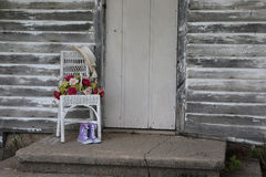 Old chair with flowers and purple shoes Stock Image