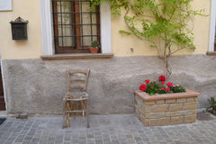 Old chair in front of house wall Stock Image