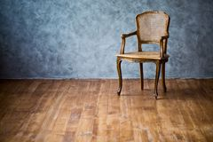 Old chair on a gray wall background. Old chair on a gray wall background stock images