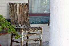 Old chair on porch. One old wooden brown and white chair on porch with a window and brick wall Royalty Free Stock Photography