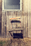 Old chair on a rustic wooden wall Royalty Free Stock Image