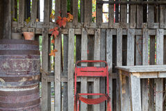 Old Chair and table outdoor. Front view of an old chair, a barrel and a table in front of a wood wall in automn tones royalty free stock images