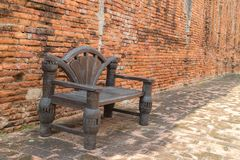 Old chair wood with the brick wall. Under sun light Royalty Free Stock Photography