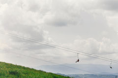 Old chairlift hoist in sunny summer mountains under blue sky and Stock Image