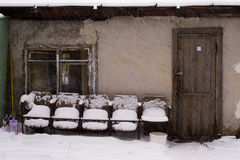 Old chairs near the house under the snow stock image