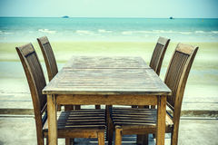 Old chairs with table and the beach Royalty Free Stock Images