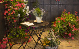 Old chairs and table in garden with many colored  flowers Stock Photos