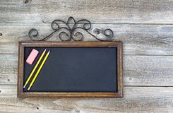 Old Chalkboard with pencils and eraser on wood Royalty Free Stock Image