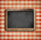 Old chalkboard on picnic tablecloth Royalty Free Stock Image