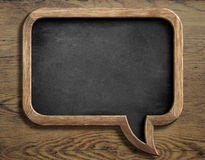 Old chalkboard in shape of speech bubble on wooden Royalty Free Stock Photography