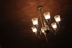 Old Chandelier in Darkened Room. An old chandelier hanging in a darkened room Royalty Free Stock Images