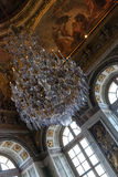 Old chandelier in Versailles. Crystal chandelier in Versailles represents the opulence and luxury of the French king's palace Stock Photos