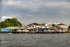 Old Chao Phraya River Thai traditional houses. Wooden slums on stilts on the riverside of Chao Praya River in Bangkok, Thailand Stock Photos
