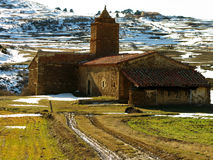 Old chapel in countryside. Scenic view of Sta Isabel Chapel in snowy countryside with Gudar mountains in background, Alcala de la Selva, Aragon, Spain Stock Photo